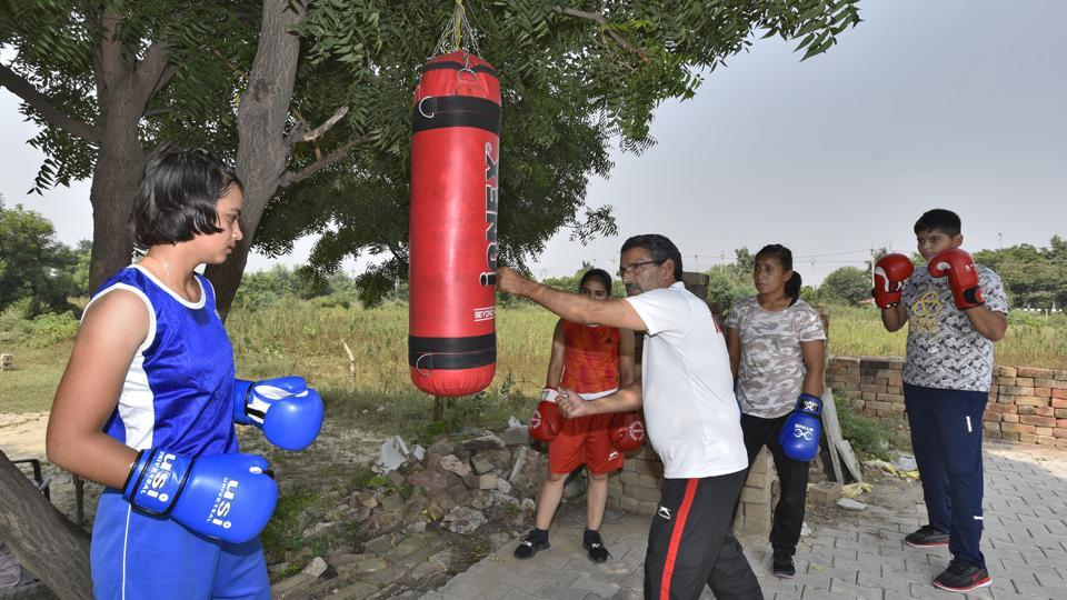 Rohtak, India - Oct. 13, 2019: Manju Rani's coach Saheb Singh Narwal is seen with young boxers at a practice area, in Rohtak, Haryana, India, on Sunday, October 13, 2019. Manju Rani settled for a silver medal after going down against Russia's Ekaterina Paltceva via 4:1 verdict in the 48kg summit clash at World Boxing Championships in Russia