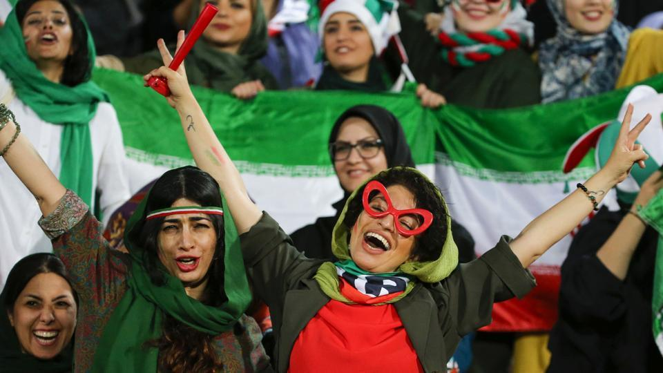 Iranian women cheer during the World Cup 2022 Group C qualification football match between Iran and Cambodia at the Azadi stadium in Tehran on October 10. The Islamic republic had barred female spectators from football stadiums for around 40 years, with clerics arguing they must be shielded from the masculine atmosphere. Women fans attended a football match freely for the first time in decades, after FIFA threatened to suspend the country over its controversial male-only policy. (Atta Kenare / AFP)