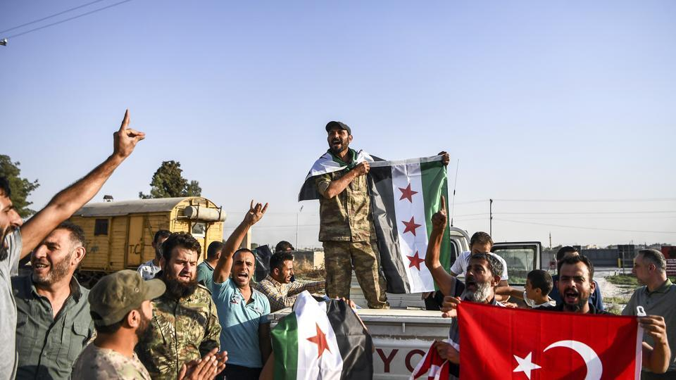 Turkish-backed Syrian opposition fighters celebrate in Akcakale, in Sanliurfa province advance, after entering over the border from Tal Abyad, Syria. State-run Anadolu news agency reported Tal Abyad had fallen to a Turkish military offensive on Sunday.
