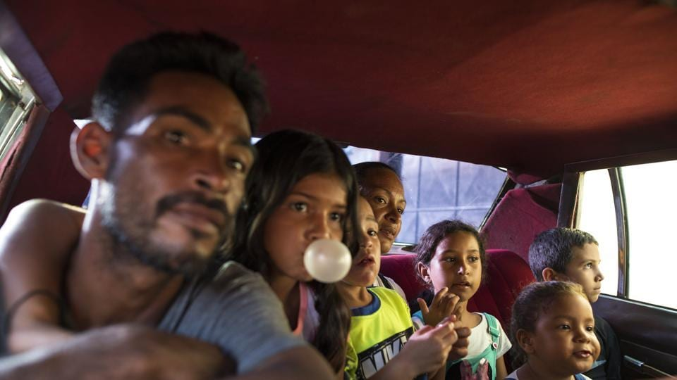 "Fisherman Yanis Rodríguez and his family ride in the back of a 1970's taxi, driven by a PDVSA state oil worker. Rodríguez used to dream of one day buying a new car and sending his eight children to private school. ""But not anymore,"" said Rodríguez, who lives on rationed electricity and struggles to find sources of clean water for washing, cooking and drinking. ""Everything is going from bad to worse.""  (Rodrigo Abd / AP)"