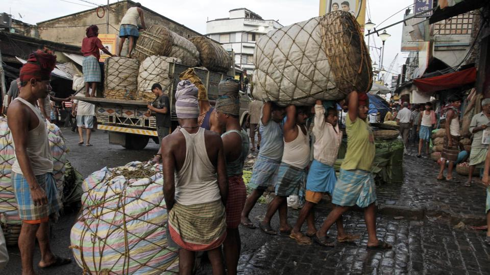 Indian laborers carry a giant basket of vegetables to a wholesale market in Kolkata, India. The world economy will grow 3% this year, down from 3.2% seen in July, IMFsaid.