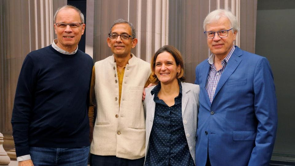 Abhijit Banerjee and Esther Duflo, two of the three winners of the 2019 Nobel Prize in Economics, pose for a photograph with 2016 Nobel Prize in Economics laureate Bengt Holstrom and 2014 laureate Jean Tirole at the Massachusetts Institute of Technology (MIT) in Cambridge, Massachusetts, U.S.