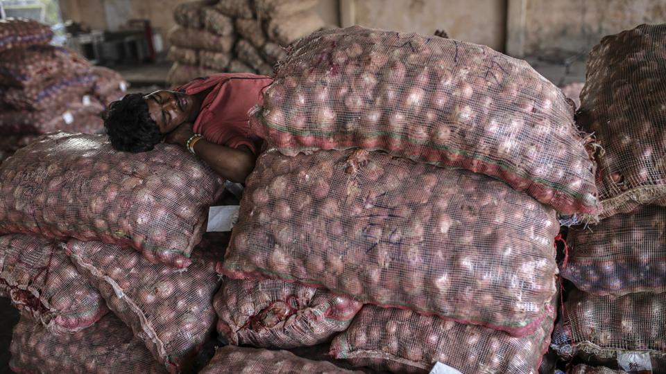 A worker sleeps on sacks of onions at the Vashi Agricultural Produce Market Committee (APMC) wholesale market in Mumbai, India, on Thursday, Oct. 3 2019. Onions in India are once more at the epicenter of a major controversy, pitting government officials who want lower prices against farmers that need extra income. Photographer: Dhiraj Singh/Bloomberg