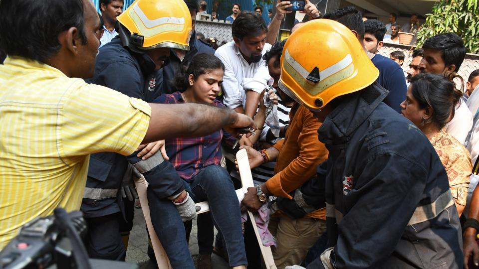 Firefighters with a woman rescued from  a commercial building in which fire broke out ,  Andheri in Mumbai, on Monday, October 14, 2019.