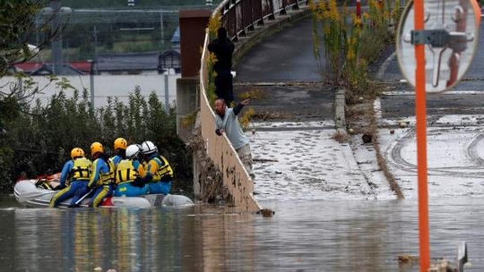 A man talks with rescue workers searching a flooded area in the aftermath of Typhoon Hagibis, which caused severe floods at the Chikuma River in Nagano, Nagano Prefecture, Japan.