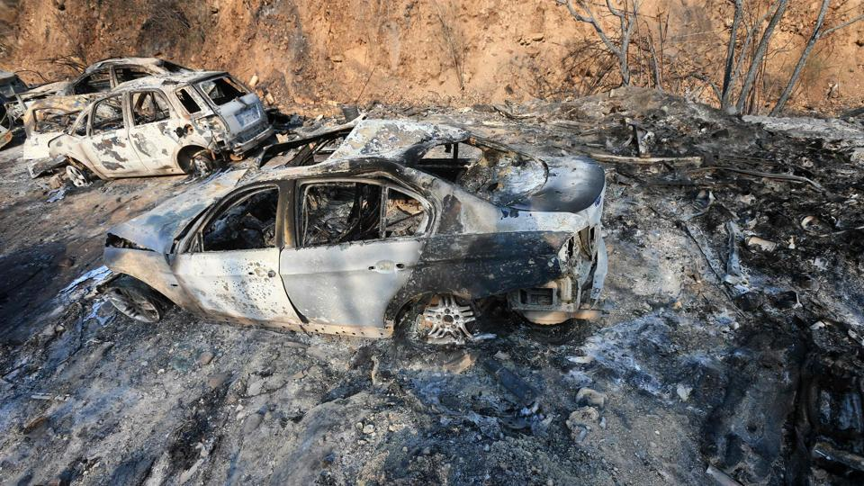 Vehicles lie on the side of a road, after they were burnt by fires near the town of Damour. The fires have left charred trees and burned-out cars and have overpowered Lebanon's fire brigades, prompting appeals to neighhouring states to send aircraft to bolster efforts. (AFP)