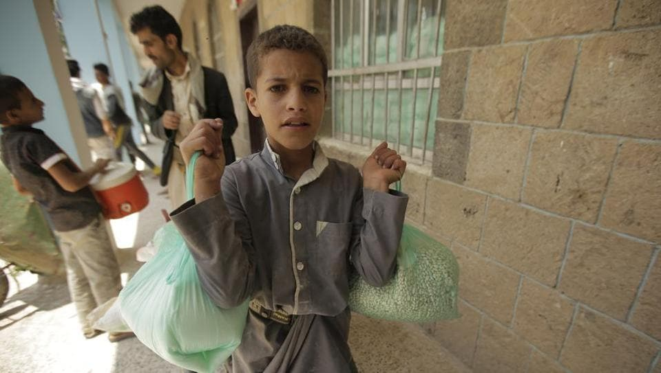 A boy carries food supplies provided by the World Food Programme at a school in Sanaa, Yemen.