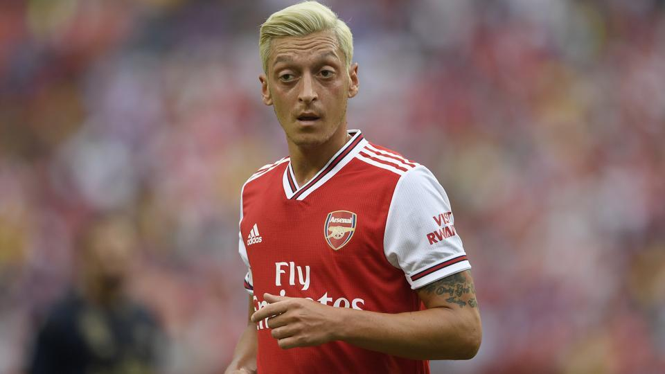 Arsenal midfielder Mesut Ozil stands on the field during the first half.