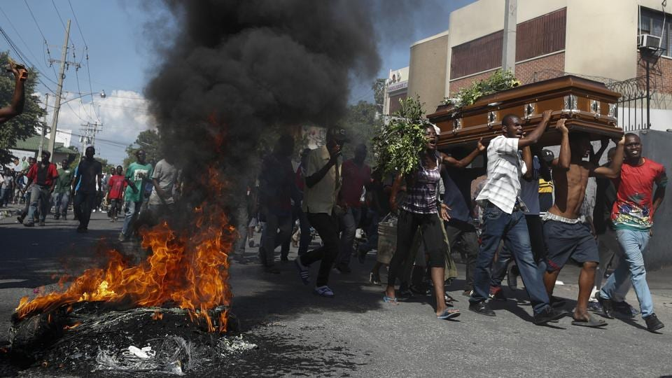 Mourners walk past burning tires carrying the coffin of a man killed during a demonstration, in Port-au-Prince, Haiti on October 16, 2019. Funerals for 11 of at least 20 people killed were held in six cities. At least two people were injured in a protest in the capital that broke out when presidential guards tried to block a road near where hundreds had gathered around the coffins of two victims. (Rebecca Blackwell / AP)