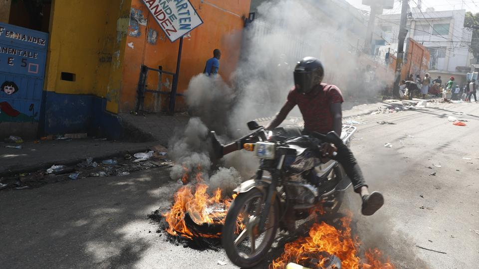 A man drives his motorcycle through a burning barricade during anti-government protests in Port-au-Prince, on October 11. Haitians have complained of a leadership vacuum given Moise's rare appearances during this crisis. The last time Moise spoke publicly before Tuesday was nearly three weeks prior in a pre-recorded 2 a.m. televised address. (Rebecca Blackwell / AP)