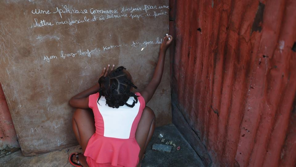 "A girl writes in French and Creole on a chalkboard: ""A sentence always begins with a capital letter and ends with a period,"" outside a one-room home in the Cite Soleil district of Port-au-Prince. Residents of Cite Soleil say access to basic services, jobs, and security has been declining and many are participating in the protests. Schools have been closed for weeks due to the protests. (Rebecca Blackwell / AP)"