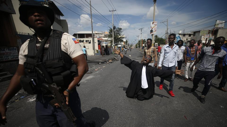 Paseus Juvensky St. Fleur, who trained as a lawyer and is now an activist working for social justice, drops to his knees as protestors trying to set up a barricade across a major road argue with police trying to stop them, in Port-au-Prince. Opposition leaders have rejected Moïse's call for unity and dialogue and created a nine-person commission they say would be responsible for overseeing an orderly transition of power. (Rebecca Blackwell / AP)