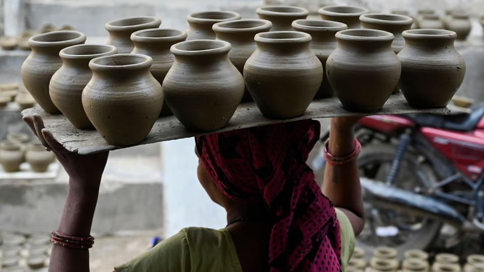 """A woman carries clay pots for drying on an open space, at Kumhar Gram in New Delhi. Known as the """"Potter's Village"""", the settlement is home to around 500 families from the traditional pottery community, who moved to the area half a century ago. (Money Sharma / AFP)"""