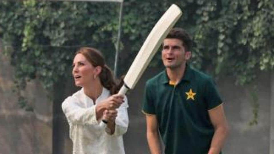 Kate Middleton plays a shot as Shaheen Afridi looks on.