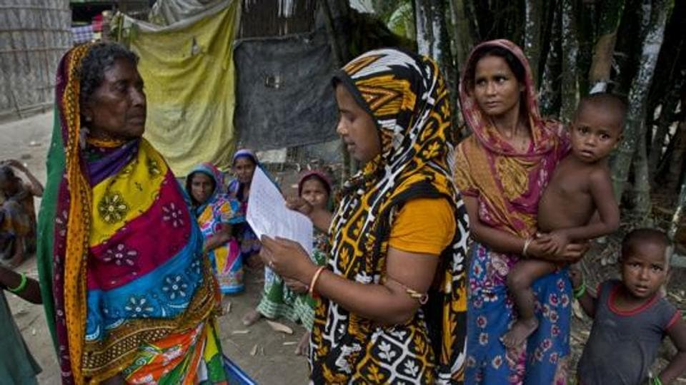 A woman checks for names in the final list of the National Register of Citizens (NRC) on a printed sheet of paper in Pabhokati village in Morigaon district, Assam.