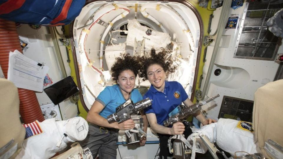 """NASA astronauts Jessica Meir (L) and Christina Koch pose for a photo in the International Space Station on Friday, ahead of their spacewalk to replace a broken battery charger. Koch and Meir made """"HERstory,"""" as NASA is calling it, with the first all-female spacewalk. (NASA / AP)"""