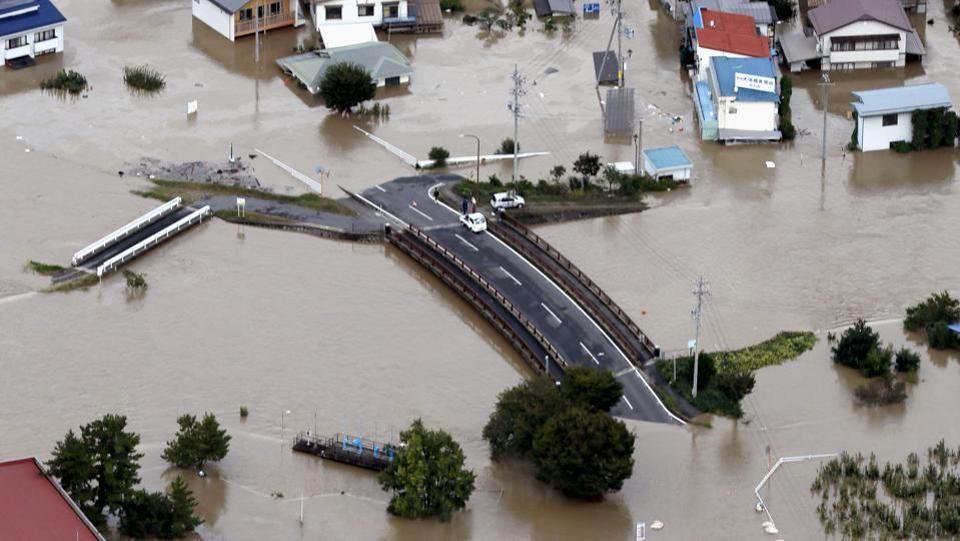 Cars are stranded on a road as the city is submerged in muddy waters after an embankment of the Chikuma River broke, in Nagano, central Japan. Rescue efforts for people stranded in flooded areas remained in full force after a powerful typhoon dashed heavy rainfall and winds through a widespread area of Japan, including Tokyo. (Yohei Kanasashi / Kyodo News via AP)