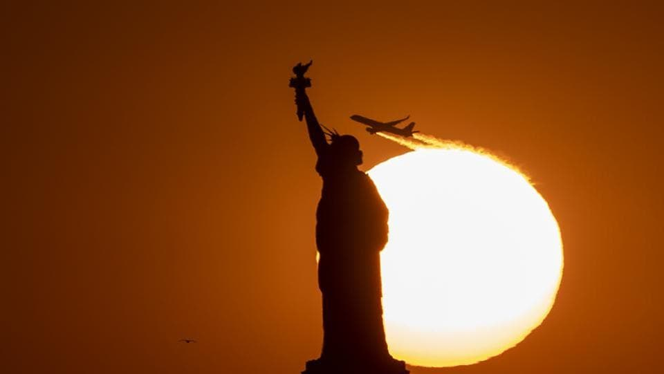 A plane flies behind the Statue of Liberty as the sun sets in New York City. (Johannes Eisele / AFP)