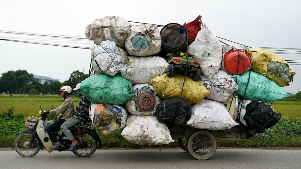 Waste collectors transport plastic scrap for recycling in the suburbs of Hanoi, Vietnam. (Nhac Nguyen / AFP)