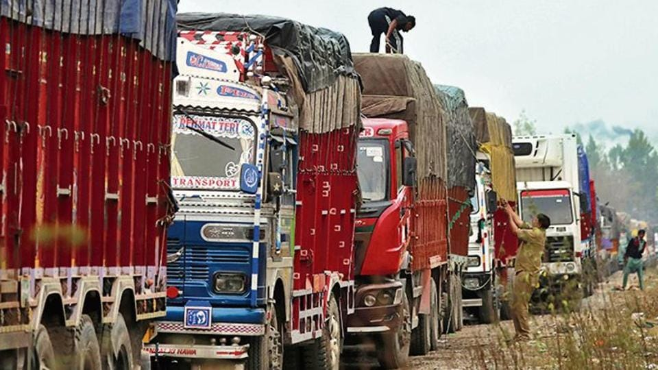 A driver covers a supply truck loaded with apples on a highway near Qazigund in Anantnag district on October 17.
