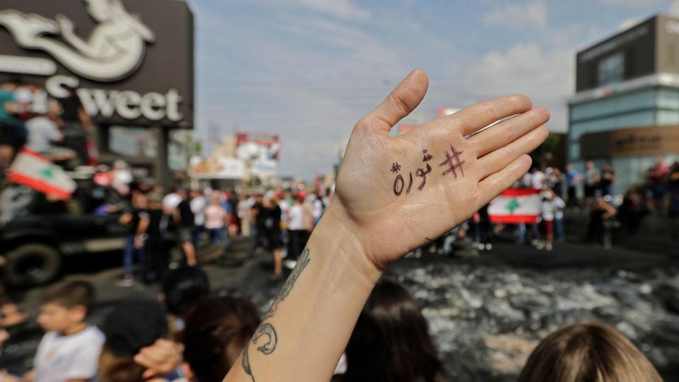 "A Lebanese demonstrator displays the word ""Revolution"" in Arabic on the palm of their hand during a protest against dire economic conditions in Zouk Mikael, north of Beirut. Public anger has simmered since parliament passed an austerity budget in July to help trim a ballooning deficit and flared on Thursday over new plans to tax calls on messaging applications such as Whatsapp, forcing the government to axe the unpopular proposal.  (Joseph Eid / AFP)"