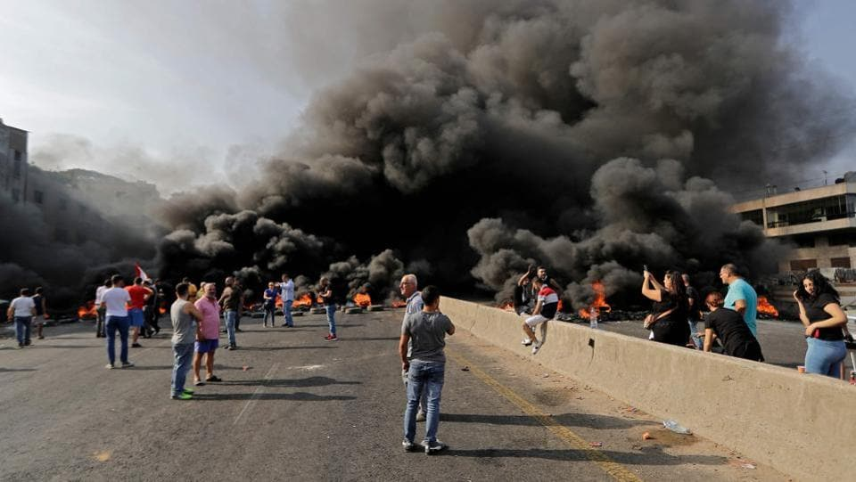 "Lebanese demonstrators gather on a highway blocked by a tire fire during a protest in Nahr Ibrahim, north of Beirut. ""We came to the streets because we can no longer bear this situation. This regime is totally corrupt,"" said Fadi Issa, 51, who was marching with his son. ""They are all thieves, they come to the government to fill their pockets, not to serve the country.  (Joseph Eid / AFP)"