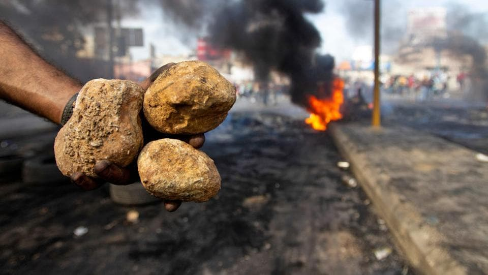 A woman walks by burning tires that were set fire to block a road during the protest. The demonstrations follow warnings by economists, investors and rating agencies that indebted Lebanon's economy and graft-entrenched financial system are closer to the brink than at any time since the war-torn 1980s. (Ibrahim Amro / AFP)