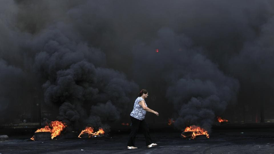 A woman walks by burning tires that were set fire to block a road during the protest. The demonstrations follow warnings by economists, investors and rating agencies that indebted Lebanon's economy and graft-entrenched financial system are closer to the brink than at any time since the war-torn 1980s. (Hassan Ammar / AP)