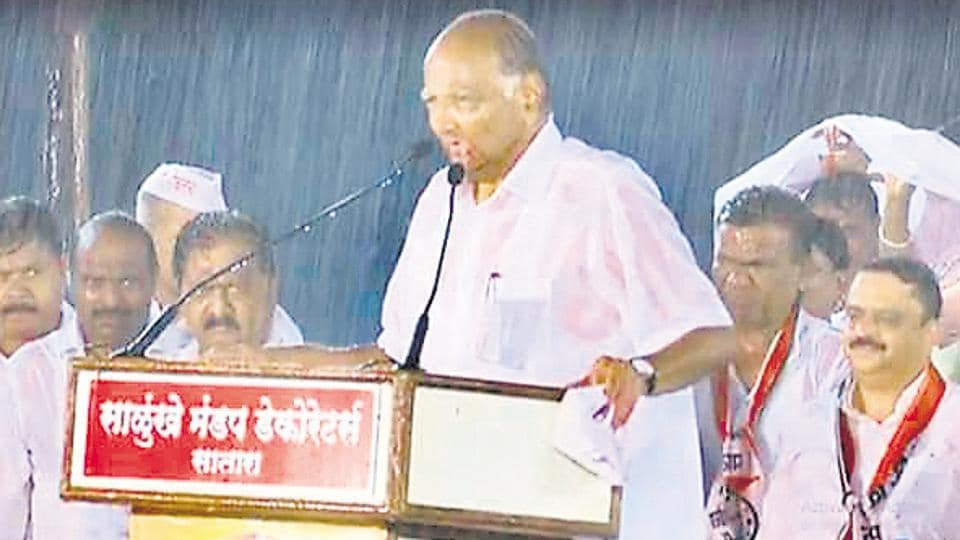 Sharad Pawar is drenched in rains while he delivers a speech in Satara on Friday.