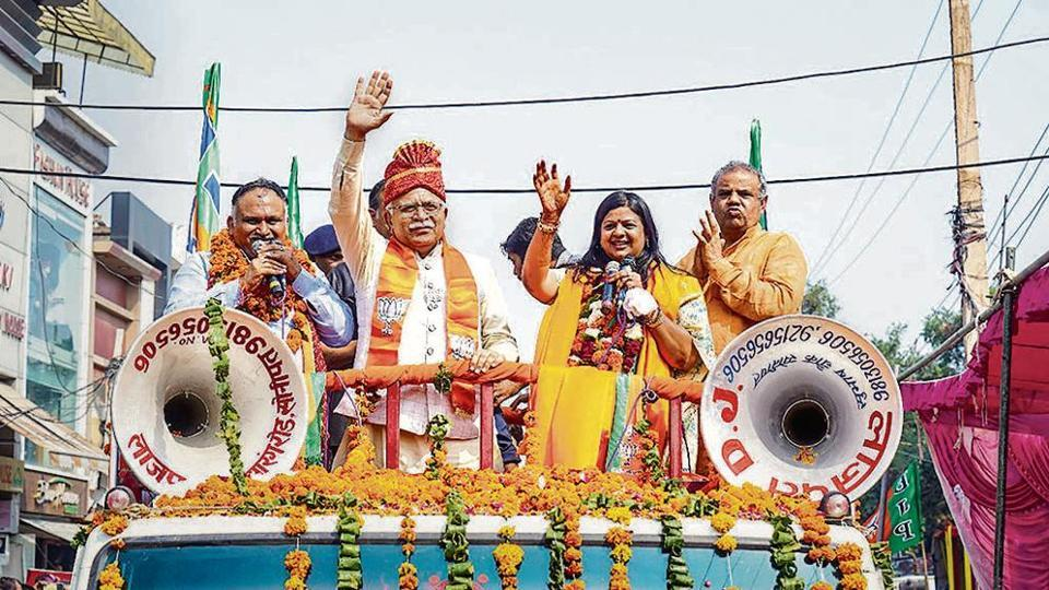 Haryana Chief Minister Manohar Lal Khattar waves at his supporters during a roadshow in support of BJP candidate Kavita Jain.