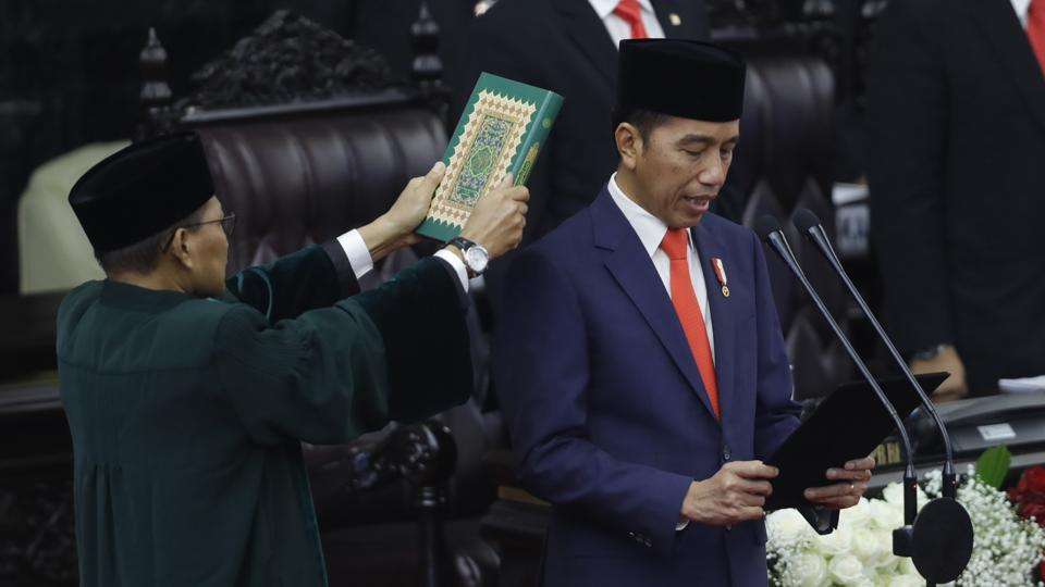 Indonesian President Joko Widodo, right, takes his presidential oath for his second five-year term during the inauguration ceremony at the parliamentary building in Jakarta.
