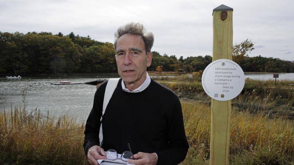Artist Thomas Starr poses next to a sign, part of a public design installation, on the banks of the Oyster River in Durham. Starr, a graphic and information design professor from Boston's Northeastern University, created the project to address possible effects of climate change.