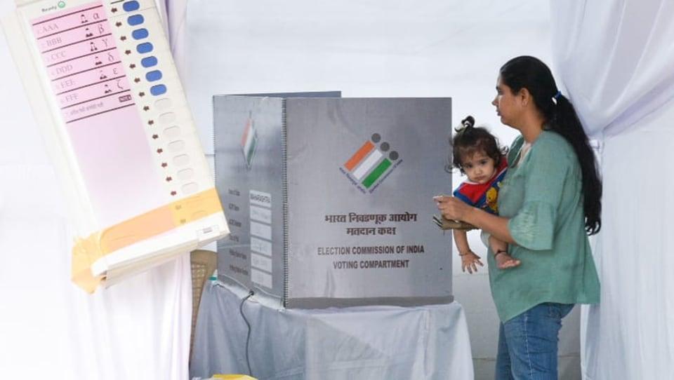 A women cast her vote along with child during Maharashtra assembly election at Mahavir Nagar , Kandivali, Mumbai, October 21, 2019.