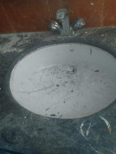 Cement strewn inside a basin in a washroom at the Thrust Theatre auditorium of the BNA in Lucknow.