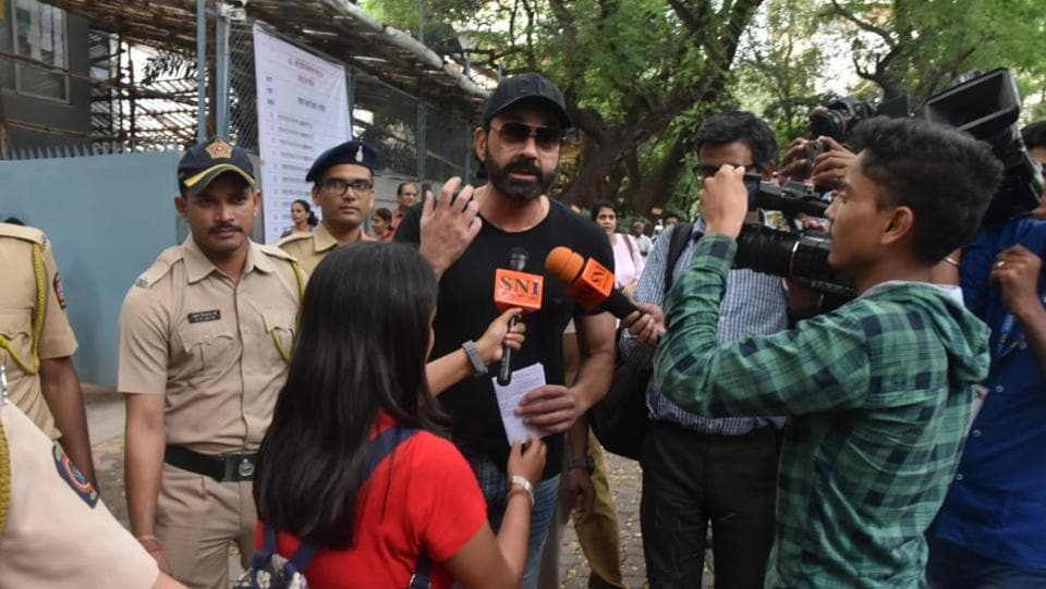 Bobby Deol talks to the media at a polling station.