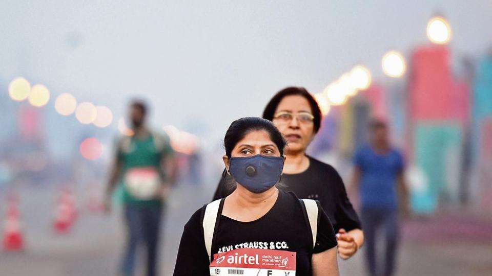 A participant seen wearing a pollution mask for protection against air pollution during the Delhi Half Marathon, near India Gate, in New Delhi, on Sunday. (Photo by Arvind Yadav/ Hindustan Times)