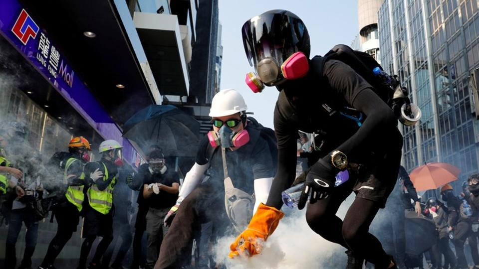An anti-government protester holds a tear gas canister during a protest in Hong Kong .