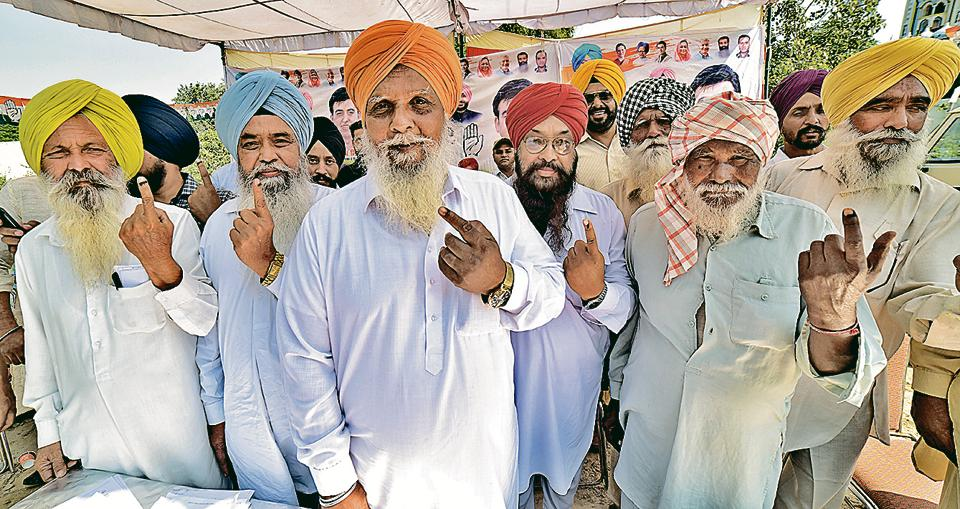 Voters show their inked fingers at a village in Dakha on Monday.