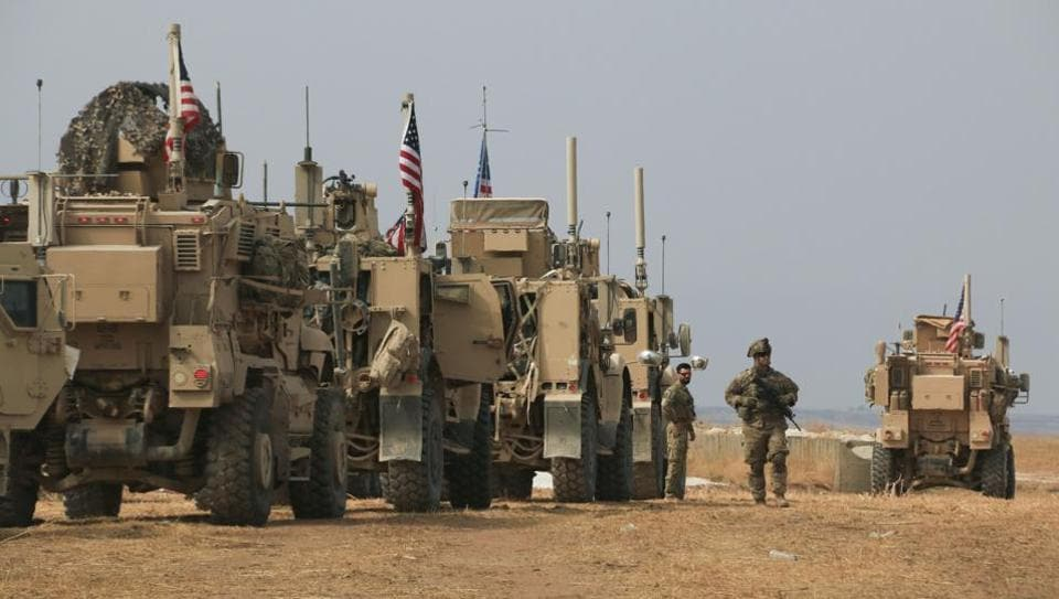 American military convoy stops near the town of Tel Tamr, north Syria. Kurdish-led fighters and Turkish-backed forces clashed sporadically Sunday in northeastern Syria amid efforts to work out a Kurdish evacuation from a besieged border town, the first pull-back under the terms of a U.S.-brokered cease-fire.