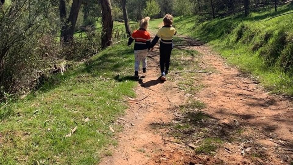 The image shows two kids walking down a trail.