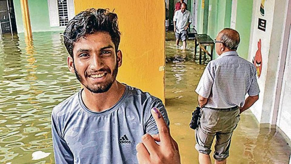 A man shows his finger marked with indelible ink after casting his vote at a polling station inundated in rain water following heavy rainfall during the bypolls for assembly seats in Ernakulam district.