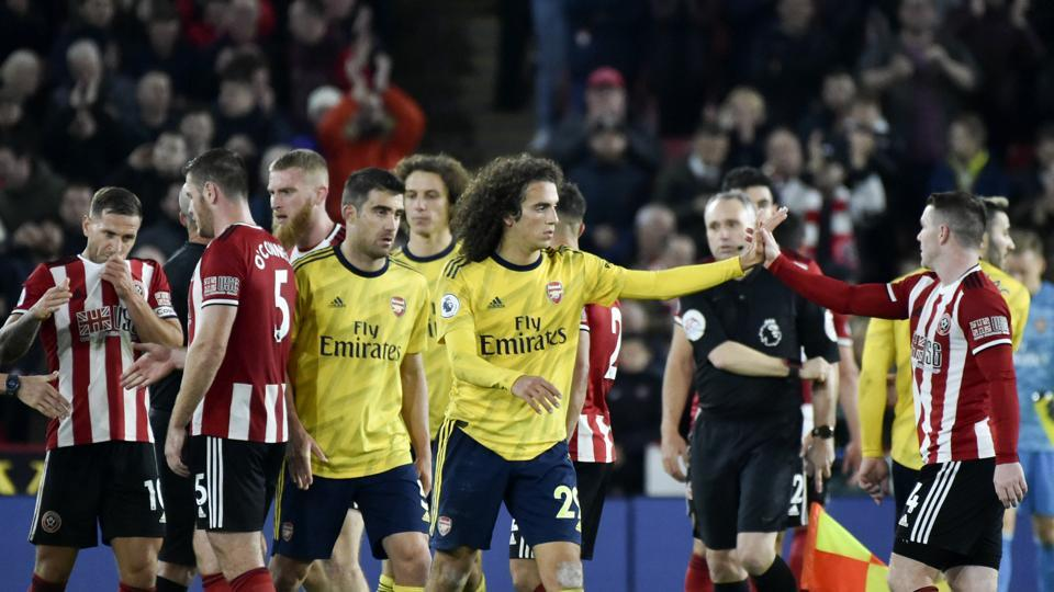 Sheffield United's and Arsenal's players react.