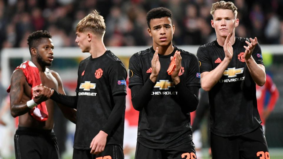Manchester United's Mason Greenwood and Manchester United's Scott McTominay applaud the fans.