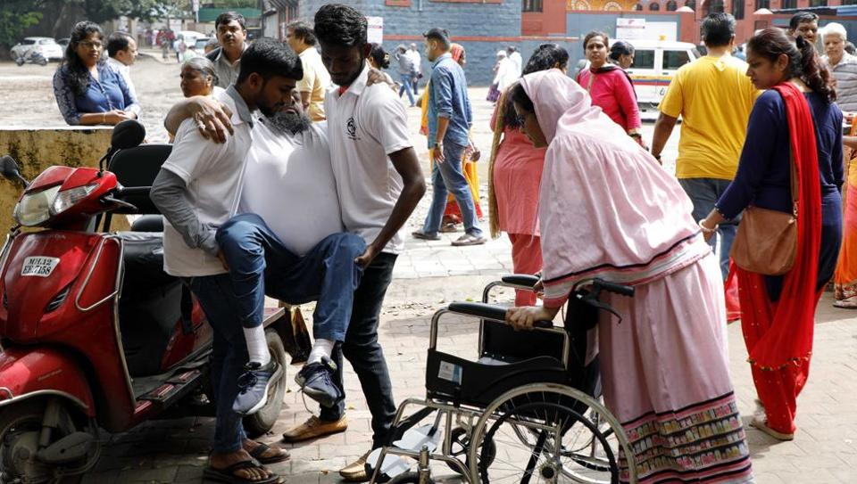 A senior citizen arrives on wheelchair to cast vote at Mahatma Phule school in Hadapsar on Monday.