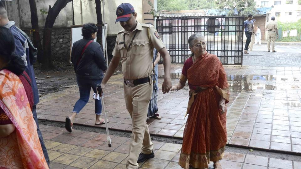 A policemen helping an old lady to go to polling booth to cast her vote.