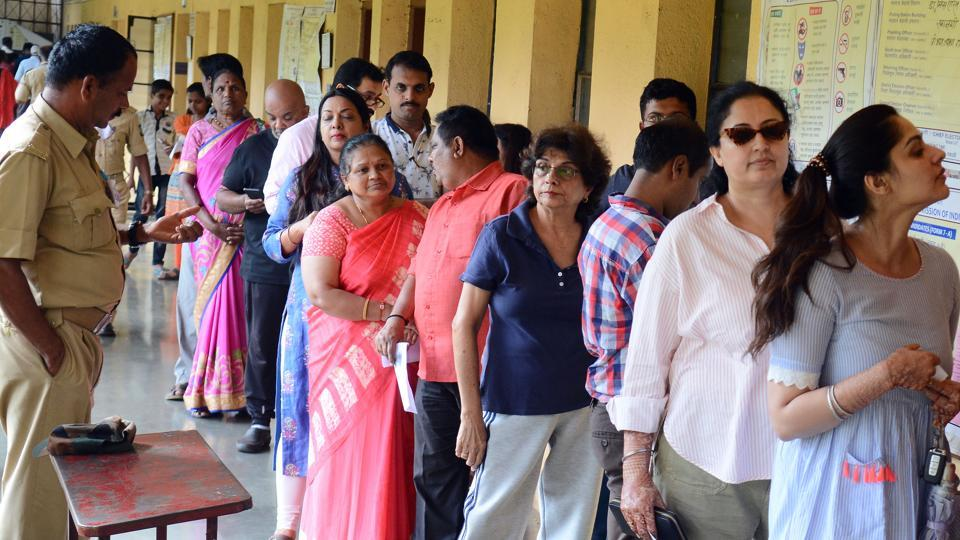 People wait in a queue to cast their votes for the assembly election.