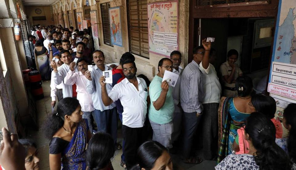 Residents pose with their electoral slips/ voter ID cards as they queue outside a polling booth at Mahatma Phule school, Hadapsar, on Monday.