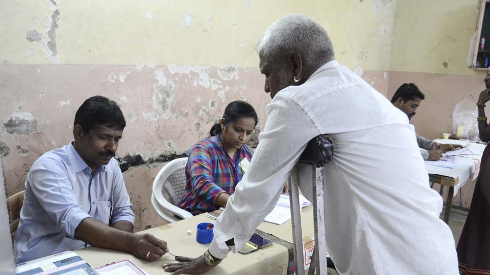 A physically challenged man is seen casting his vote.