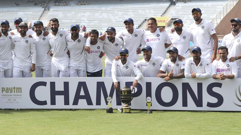 Members of Indian team pose with the winners trophy after their win.