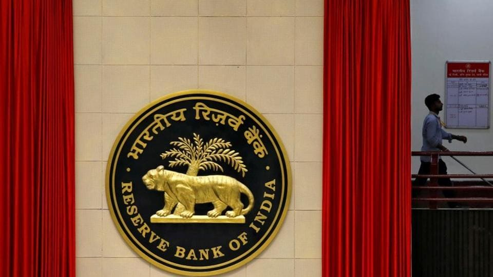 A worker walks past the logo of Reserve Bank of India (RBI) inside its office in New Delhi.
